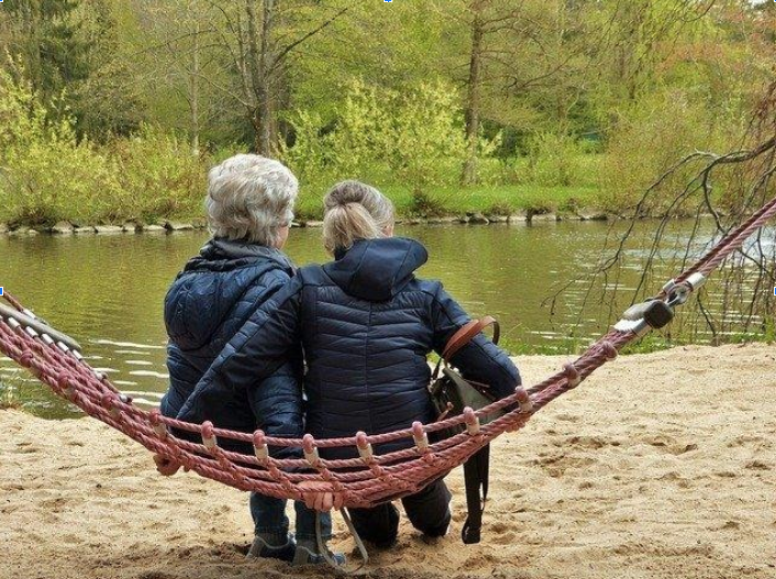 A woman and her mother with dementia sitting on a hammock at a lake